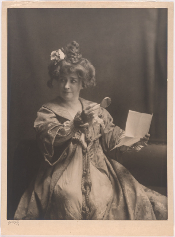 Black and white portrait of Minne Maddern Fiske, holding a letter and magnifying glass.