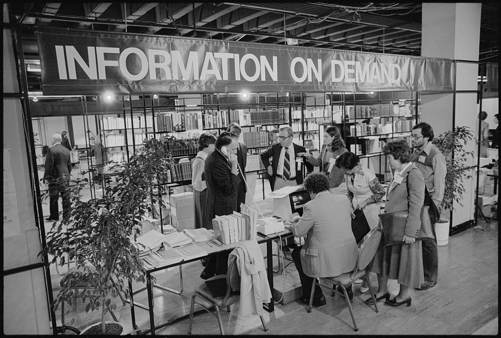 """Black and white photograph of a man using computer as others watch at a exhibit with banner """"Information on Demand"""", at the White House Conference on Library and Information Services, Washington, D.C."""